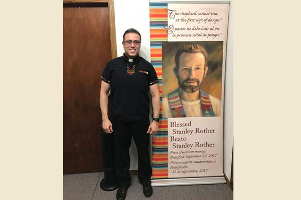 Pastor Father Salvador Márquez-Muñoz stands by a banner honoring Blessed Stanley Rother, patron of the church in Decatur. Parishioners celebrated his feast day Mass July 28. (Courtesy Father Salvador Marquez-Munoz)