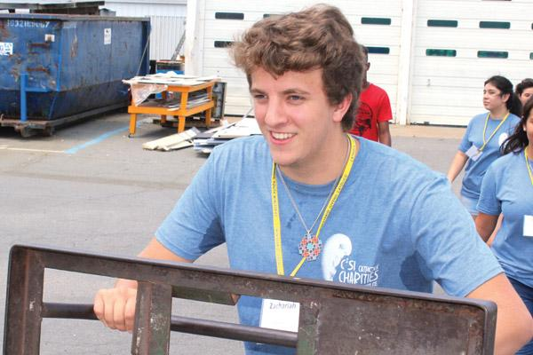 Zachariah Neumeier leads his C2SI teammates to complete a sweltering community service assignment. (Dwain Hebda photo)