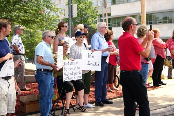 Christians stand across the street from the State Capitol Aug. 16 during the Rally for the First Amendment, holding signs with Ten Commandments and other Bible verses, to protest the presence of the satanic statue. (Malea Hargett photo)