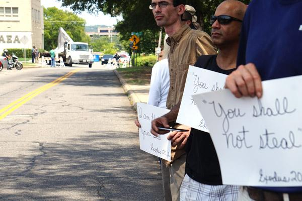 Protesters hold signs with Bible verses as a truck carrying the covered Baphomet statue made its way toward the State Capitol for the First Amendment Rally Aug. 16 organized by The Satanic Temple. The temple objected to the 10 Commandments monument on Capitol grounds. (Aprille Hanson photo)