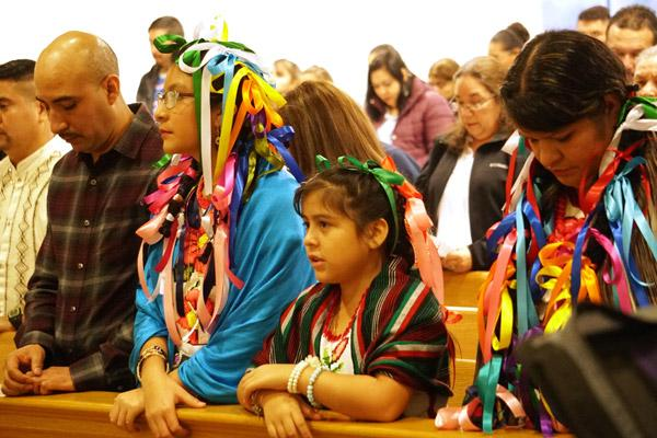 Juan and Luz Chavez, (left) their daughter Marialy Chavez and Juan's sister Maria Chavez pray during the Our Lady of Guadalupe Mass Dec. 8 at Holy Spirit Church in Hamburg. (Malea Hargett photo)