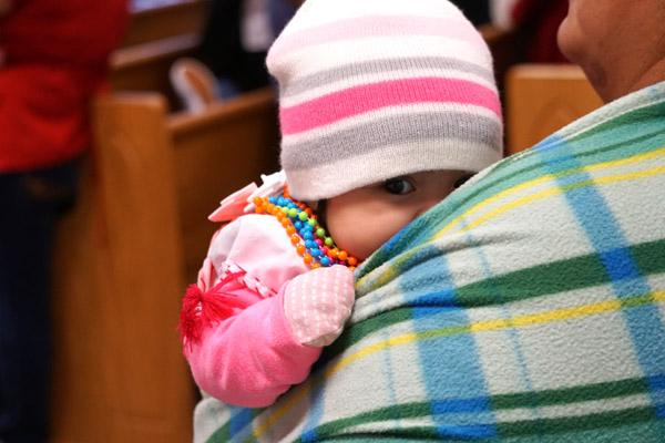 A baby sneaks a peek over her mother's shoulder during the Our Lady of Guadalupe Mass Dec. 8. (Malea Hargett photo)
