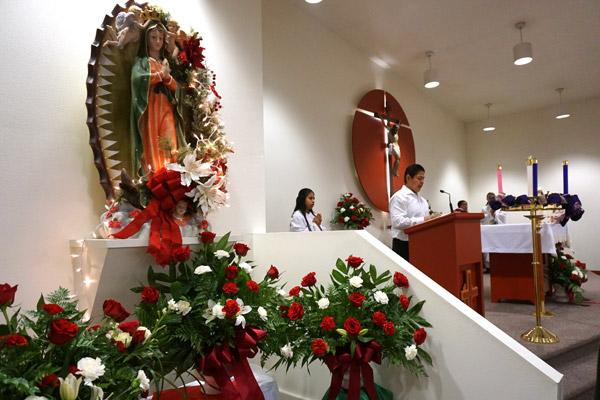 Red and white roses and carnations surround the statue of Our Lady of Guadalupe during Mass Dec. 8 at Holy Spirit Church in Hamburg. (Malea Hargett photo)