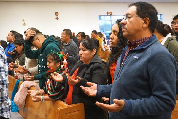 Hector Mondragon (right) and others pray the Our Father during the Dec. 8 Mass. (Malea Hargett photo)