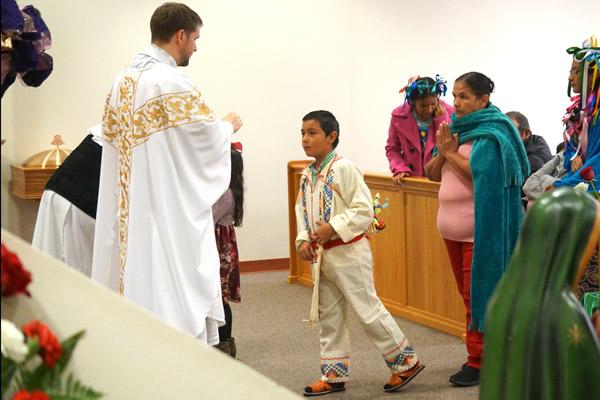 A young parishioner dressed in traditional Mexican clothing approaches pastor Father Stephen Hart for Communion. (Malea Hargett photo)