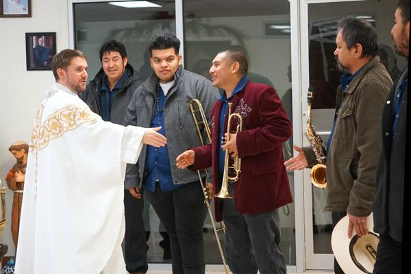 Pastor Father Stephen Hart greets the Tamborazo Zacatecano de Arkansas band before they begin performing after Mass. (Malea Hargett photo)