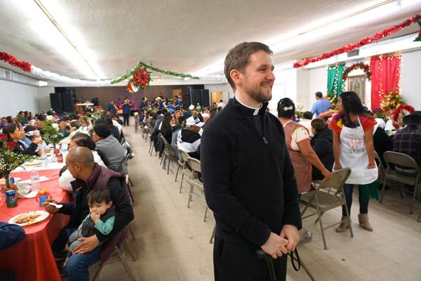 Pastor Father Stephen Hart pauses for a photo during the fiesta at the Ashley County Fairgrounds following the Our Lady of Guadalupe feast day Mass while a Russellville band called Tamborazo Zacatecano de Arkansas performs at the other end of the hall. (Malea Hargett photo)