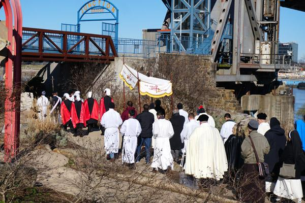 A seminarian carrying a cross and the Fourth Degree Knights of Columbus lead the procession near the Arkansas River.  (Malea Hargett photo)