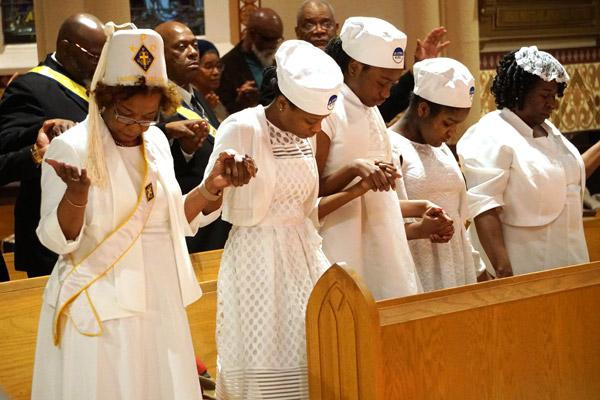 Junior Daughters of St. Peter Claver pray the Our Father during the MLK Mass Jan. 19. (Malea Hargett photo)