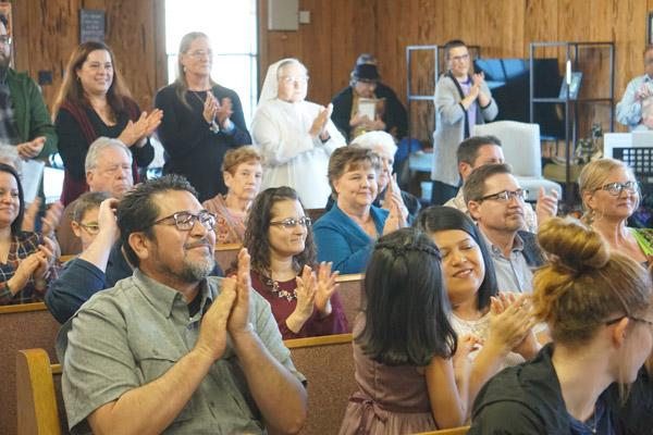 Congregants applaud after Bishop Taylor establishes an official Catholic community of Greenbrier during the March 16 Mass. The Mass was held eight days ahead of St. Oscar Romero's March 24 feast day. (Aprille Hanson photo)