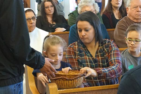 The faithful donate toward their new community during the offering. In order to one day be established as a parish, the community will have to be able to support itself financially. (Aprille Hanson photo)