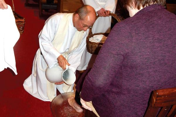 Father William Elser washes a parishioner's feet at Sacred Heart of Jesus Church during Holy Thursday Mass April 18 in Hot Springs Village. (Jim Keary photo)