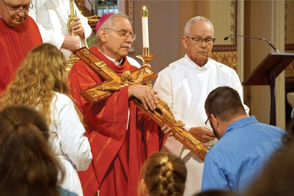 Bishop Anthony B. Taylor holds a wooden crucifix for parishioners to kiss during the Good Friday service at the Cathedral of St. Andrew in Little Rock. (Malea Hargett photo)