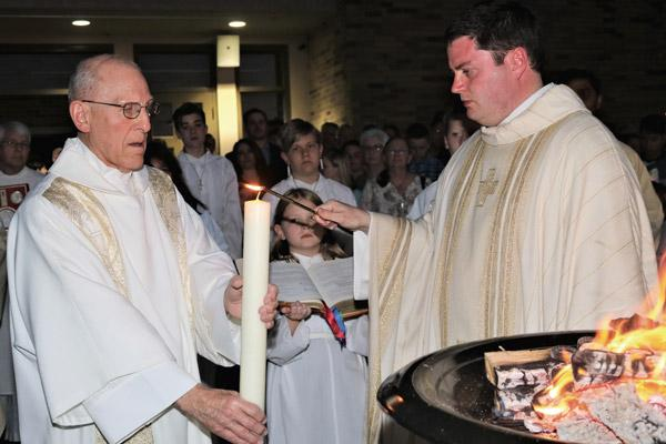 Pastor Father Tony Robbins lights the Paschal candle held by Deacon Richard Papini in photo at right as they stand next to the Holy Saturday Easter fire, April 20 at St. Joseph Church in Conway. (Photo not for sale)