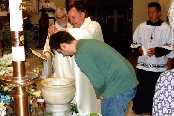 Father George Sanders, pastor of St. Mary of the Springs Church in Hot Springs, baptizes Ryan Burton during the Easter Vigil Mass on Holy Saturday, April 20. (Jim Keary photo)