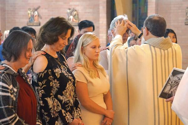 Father Norbert Rappold, pastor of St. Peter the Fisherman Church in Mountain Home, blesses candidate Harriett Feulner during confirmation at Easter Vigil Mass April 20 in photo above. Other candidates pictured are Carol McClain (left), Nancy Bemus and Ashton Garner. (Aprille Hanson photo)