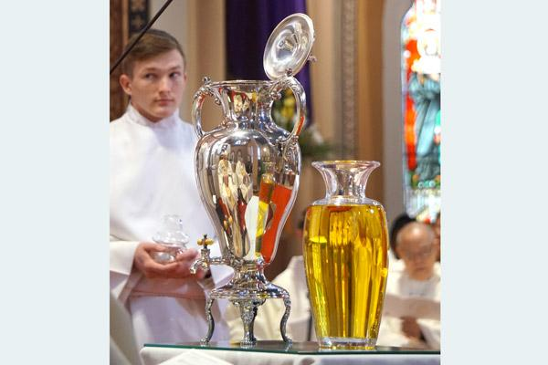 The oil of catechumens, used in the baptism of infants, is placed in front of Bishop Taylor at the Chrism Mass by seminarian Joseph Jones (left), waiting for a blessing. (Aprille Hanson photo)