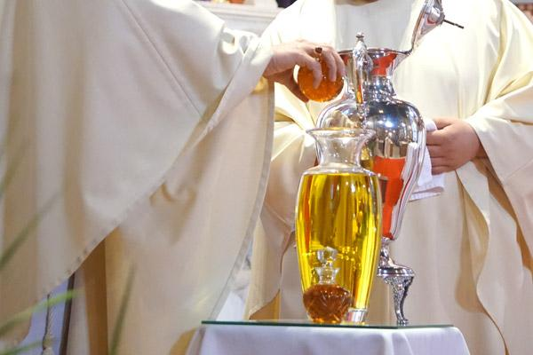 Bishop Taylor pours the fragrance into the olive oil to create the sacred chrism before consecrating it at the Chrism Mass. Chrism is the only oil of the three to be consecrated with the Holy Spirit. (Aprille Hanson photo)
