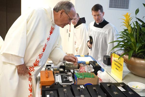 Deacon Tom Pohlmeier (left) searches for his holy oils to bring back to St. Joseph Church in Paris, as Father Paul McCambridge, FSSP, of Cabot moves closer to begin his search. Following the Chrism Mass April 15, priests and deacons pick up their containers of oils for the year. (Aprille Hanson photo)