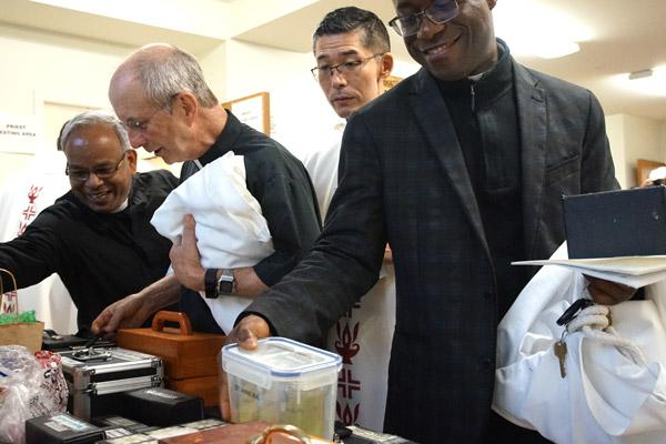 After the Chrism Mass at the Cathedral of St. Andrew, priests flood into McDonald Hall to pick up their filled containers of oil for the year. Priests pictured are Father Aby Abraham, IMS (left), Father Bill Elser, Father Toshio Sato, CM, and Father Joseph Archibong. (Aprille Hanson photo)