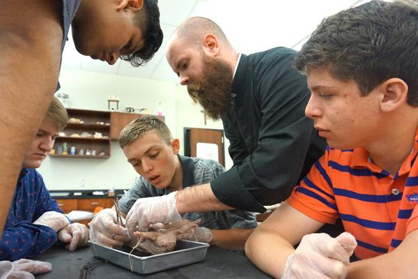"Father Patrick Friend, 30, helps his sophomore biology students dissect a fetal pig in lab at Catholic High School in Little Rock May 2. From playing the latest video games to sitting with students at lunch, he lets students know he's ""genuinely interested"" in their lives. (Aprille Hanson photo)"