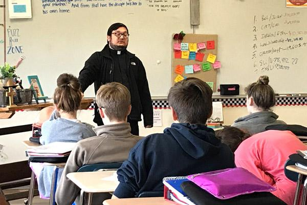 Father Stephen Elser, 28, answers questions about faith and morality from eighth-grade religion students at Fort Smith's Trinity Junior High School in October. He said it's important to be himself and show how normal it is to be a priest. (Courtesy Eileen Teagle, Trinity Junior High)