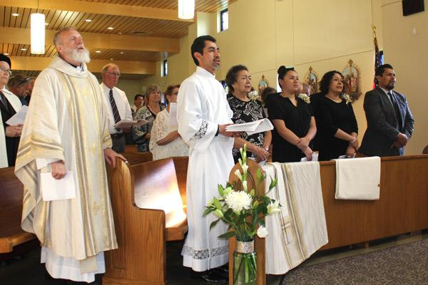 Daniel Velasco, center, sings along with his family and Vocations Director Msgr. Scott Friend (left) during Velasco's May 17 diaconate ordination Mass in Searcy. (Dwain Hebda photo)