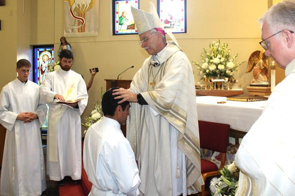 Bishop Anthony B. Taylor lays his hands on Daniel Velasco, ordaining him a transitional deacon. Velasco is the first vocation produced by St. James Church in Searcy. (Dwain Hebda photo