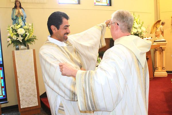 With the assistance of Brother Luke Turner, OSB, of St. Benedict Abbey in Kansas, Daniel Velasco slips on the vestments of a deacon during his May 17 ordination Mass. (Dwain Hebda photo)