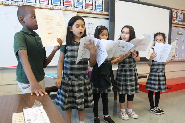 "A group of Amanda Bridges' second-graders entertain their classmates at St. Edward School in Little Rock with a reading of the appropriately-titled ""I'll Be The Dragon."" They are (from left) Bonito Jovonang, Alysson Rodriguez, Fatima Gonzalez, Baylee Garcia and Daniela Ventura. (Dwain Hebda photo)"