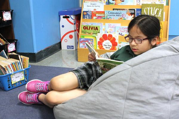 Sophia Varela gets lost in a good book during afternoon reading time in Elizabeth Krupsaw's first-grade classroom at St. Edward School in Little Rock. (Dwain Hebda photo)
