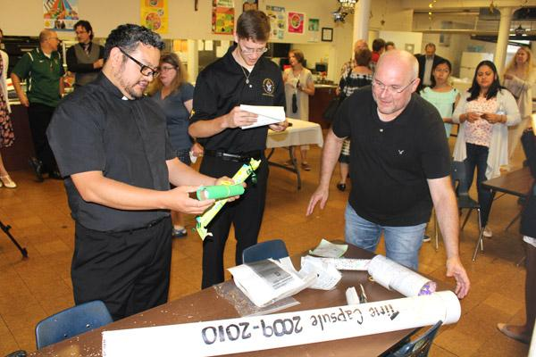 St. Edward pastor Father Juan Manjarrez (left) and diocesan seminarian John Paul Hartnedy, a St. Edward School graduate, inspect the contents of a 2010 school time capsule with Scott Sparks after the alumni Mass May 19. (Dwain Hebda photo)