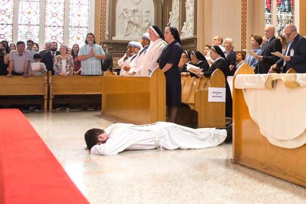 Jon Miskin lays prostrate as his family watches and the congregation sings the Litany of the Saints. (Bob Ocken photo)