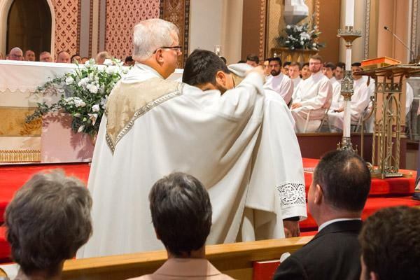 His pastor Msgr. Francis Malone assists Father Jon Miskin in putting on the vestments of a priest, including a stole and chasuble. (Bob Ocken photo)