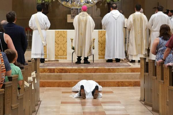 As the congregation sings the Litany of the Saints, Joseph Friend lays prostrate before the altar. (Malea Hargett photo)