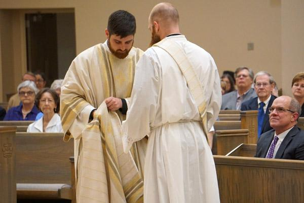 Deacon Jon Miskin, who was ordained a priest three days later, helps vest Joseph Friend with the stole and dalmatic worn by a deacon. (Malea Hargett photo)