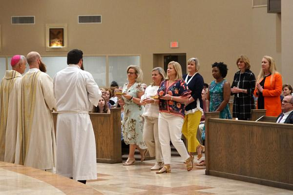 Seven friends of Joseph Friend's late mother Betty were chosen to bring up the gifts during Mass. (Malea Hargett photo)
