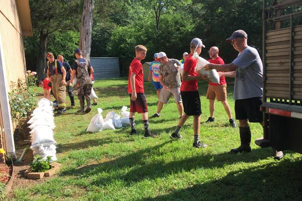Youth from New Life Church in Greenbrier and members of the Greenbrier Fire Department help stack sandbags along the home of Bruce and Juanita Noah, members of St. Joseph Church in Conway, June 1. (Courtesy Juanita Noah)