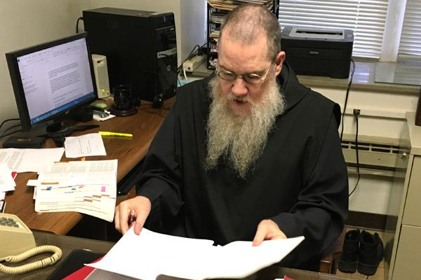 Brother Roch McClellan, oblate director for Subiaco Abbey, works in his office June 13. He is one of only three monks at the abbey currently sporting a long beard. (Photo by Brother Ephrem O'Bryan, Subiaco Abbey)