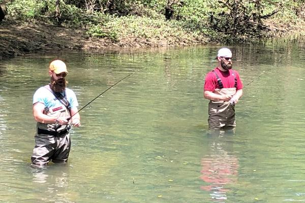 "Father Patrick Friend (left) and Father Jeff Hebert fish in the Little Red River at Pangburn June 10. While it began as a ""beard off"" competition in semi-nary, they have continued growing out long beards. (Courtesy Father Mauricio Carrasco)"