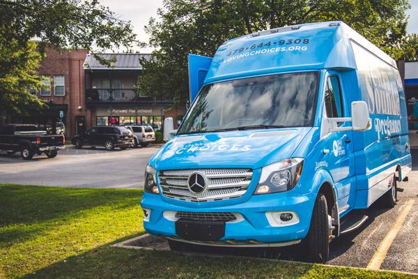 The Loving Choices ultrasound bus, nicknamed Alexandra, shares the parking lot with Planned Parenthood on the clinic's last day of business. Alexan-dra is named after a child whose life was saved from abortion. (Travis McAfee photo)
