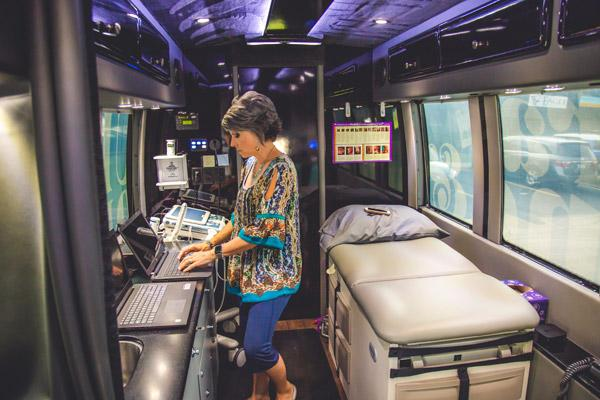 Nicole Johnson, a Loving Choices mentor who also fills in driving the bus, shows ultrasound equipment used to help pregnant women see their unborn babies. (Travis McAfee photo)