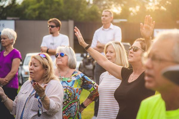 Some of the more than 100 people who gathered to pray in front of the former Planned Parenthood clinic in Fayetteville include Molly Mays (at left with hands open) and Merry Beth Anderson (with hands raised). (Travis McAfee photo)