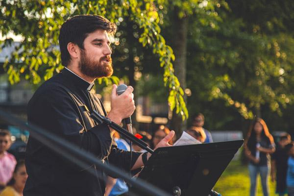 "Father Jon Miskin, associate pastor of St. Raphael Church in Springdale, offers the closing prayer July 25, exhorting the people, ""If you have any doubt as to the power and faithfulness of God, remember this night."" (Travis McAfee photo)"