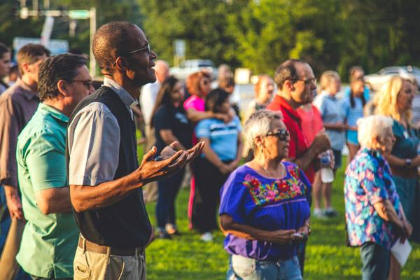 Father Eliseo Noel Njopmo, associate pastor at St. Joseph Church in Fayetteville, prays with more than 100 other people during a prayer vigil outside the now-closed Planned Parenthood clinic in Fayetteville July 25. (Travis McAfee photo)