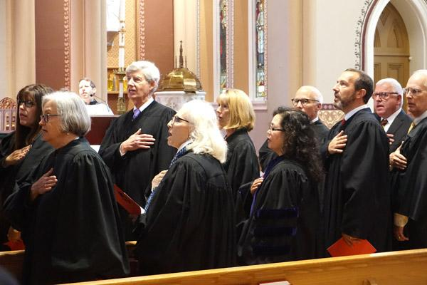 "Judges salute the American flag while singing the Star Spangled Banner ahead of the 25th annual Red Mass at the Cathedral of St. Andrew in Little Rock on Oct. 4, hosted by the St. Thomas More Society. Pictured are (left to right): Stephanie Casady, Saline County District judge; Susan Weber Wright, Federal District judge; Wayne Gruber, Pulaski County District judge; Mary McGowan, Sixth Judicial Circuit judge; Rita Gruber, chief justice of the Arkansas Court of Appeals; Jessie Wallace Burchfield, Associate Dean of the William H. Bowen School of Law in Little Rock; Milas ""Butch"" Hale, Sherwood district judge; Andy Gill, District Court judge of Perry County; Paul Keith Arkansas Bar Association president elect; and Chaney Taylor, Batesville District Court judge. (Aprille Hanson photo)"