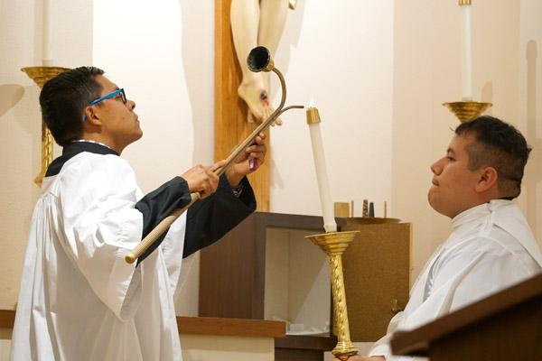 Altar servers, including seminarian Pablo Quintana of Magnolia (right), light the altar candles during the special rituals. (Malea Hargett photo)