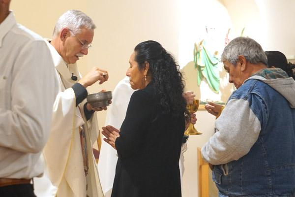 Bishop Anthony B. Taylor distributes Communion during the bilingual Mass Nov. 23 at St. Luke Church in Warren. (Malea Hargett photo)
