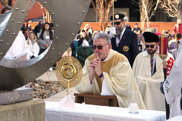 Father John Connell, vicar general and pastor of St. Raphael Church in Springdale, prays before the Blessed Sacrament during one of the stops on the procession. (Malea Hargett photo)
