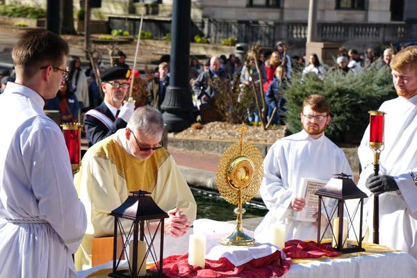 At each station, Father John Connell kneels and prays before the Blessed Sacrament, assisted by seminarians. Processors pray in the background in front of the DoubleTree Hotel in downtown Little Rock. (Malea Hargett photo)
